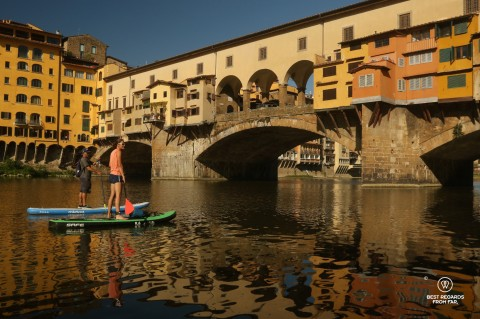 Stand up paddling the Arno River by the Ponte Vecchio in Florence, Italy