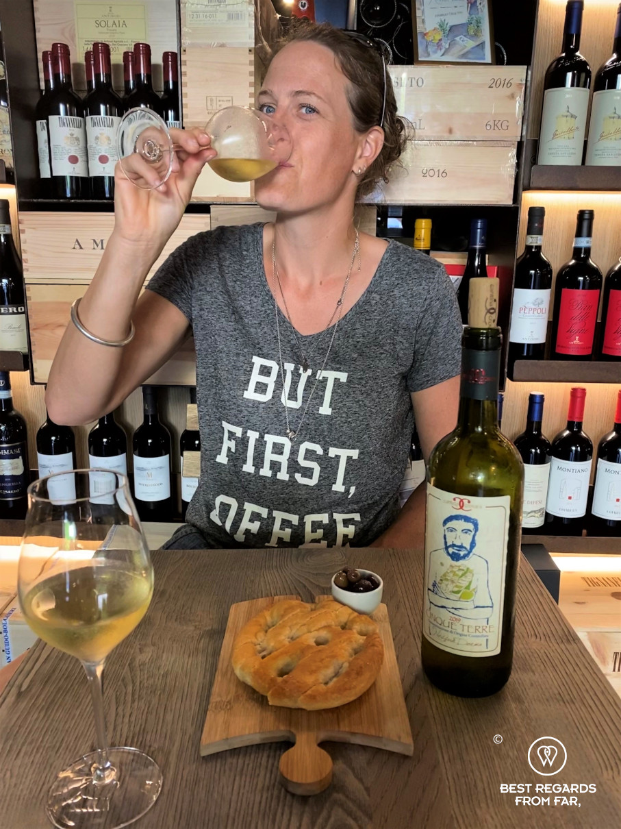 Woman tasting white wine in a wine bar in Italy