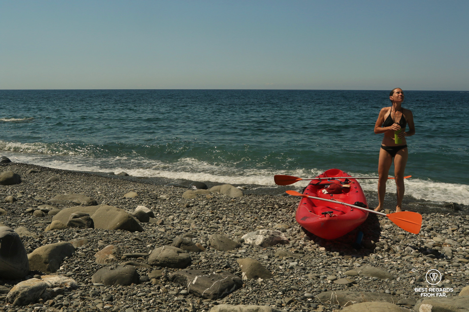 Woman in biking next to her red kayak on a rocky beach and the sea