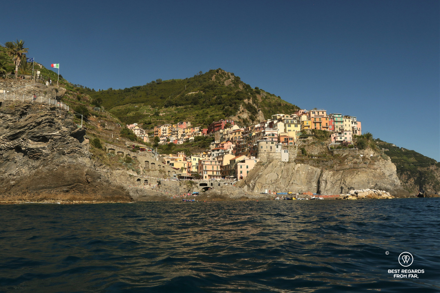 Colourful houses of Manerola seen from the sea with blue skies