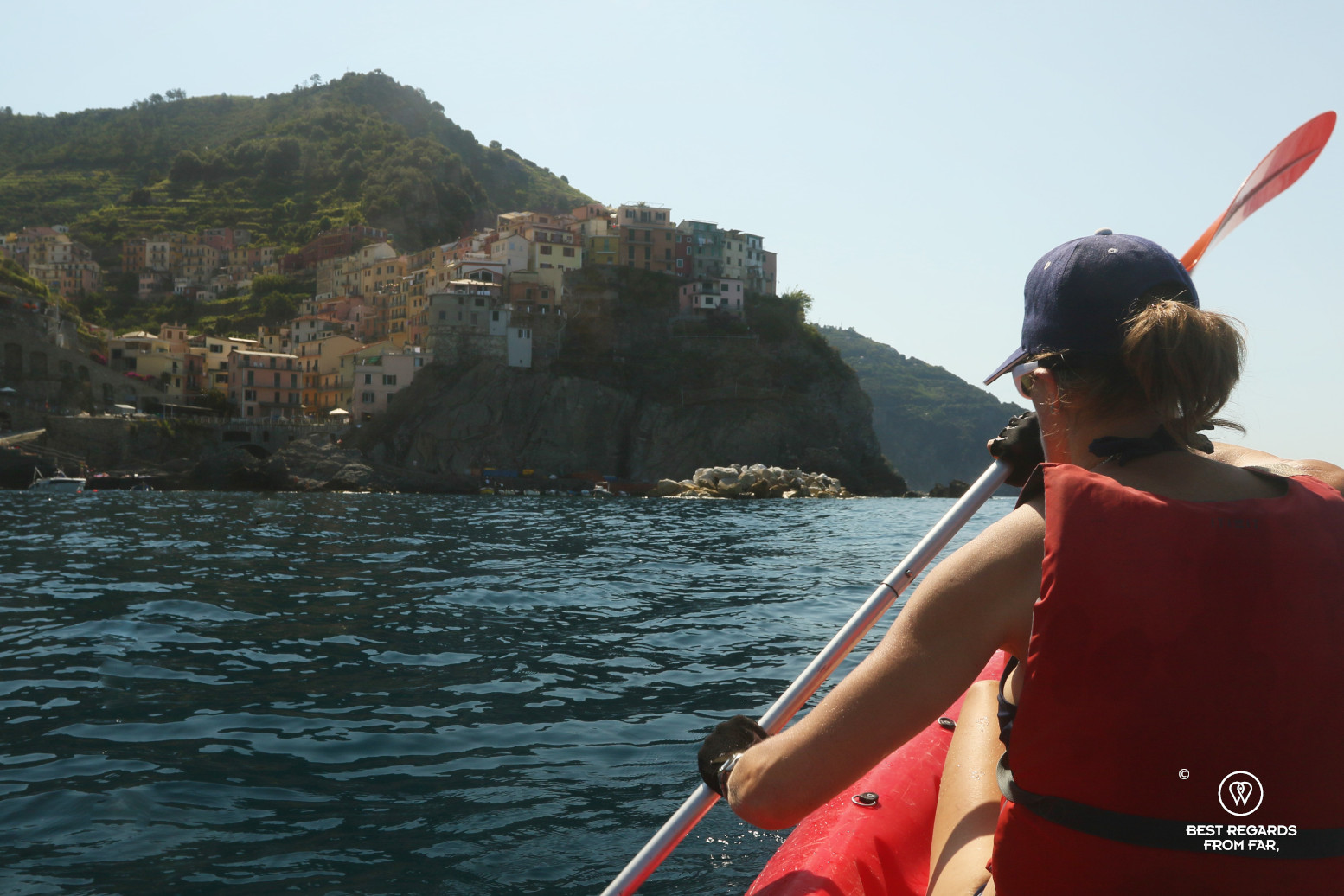 Woman kayaking on the sea by a village built on a cliff