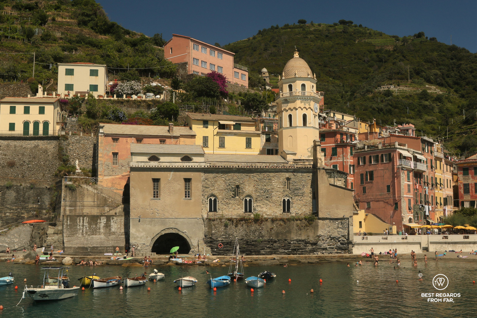 Small boats in the harbour of Vernazza, Italy with old houses and green mountains