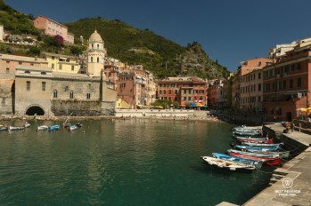 Boats in the quiet harbour of Cinque Terre with green mountains and blue skies
