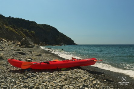 Red kayak on a rocky beack, the sea and blue skies, no people