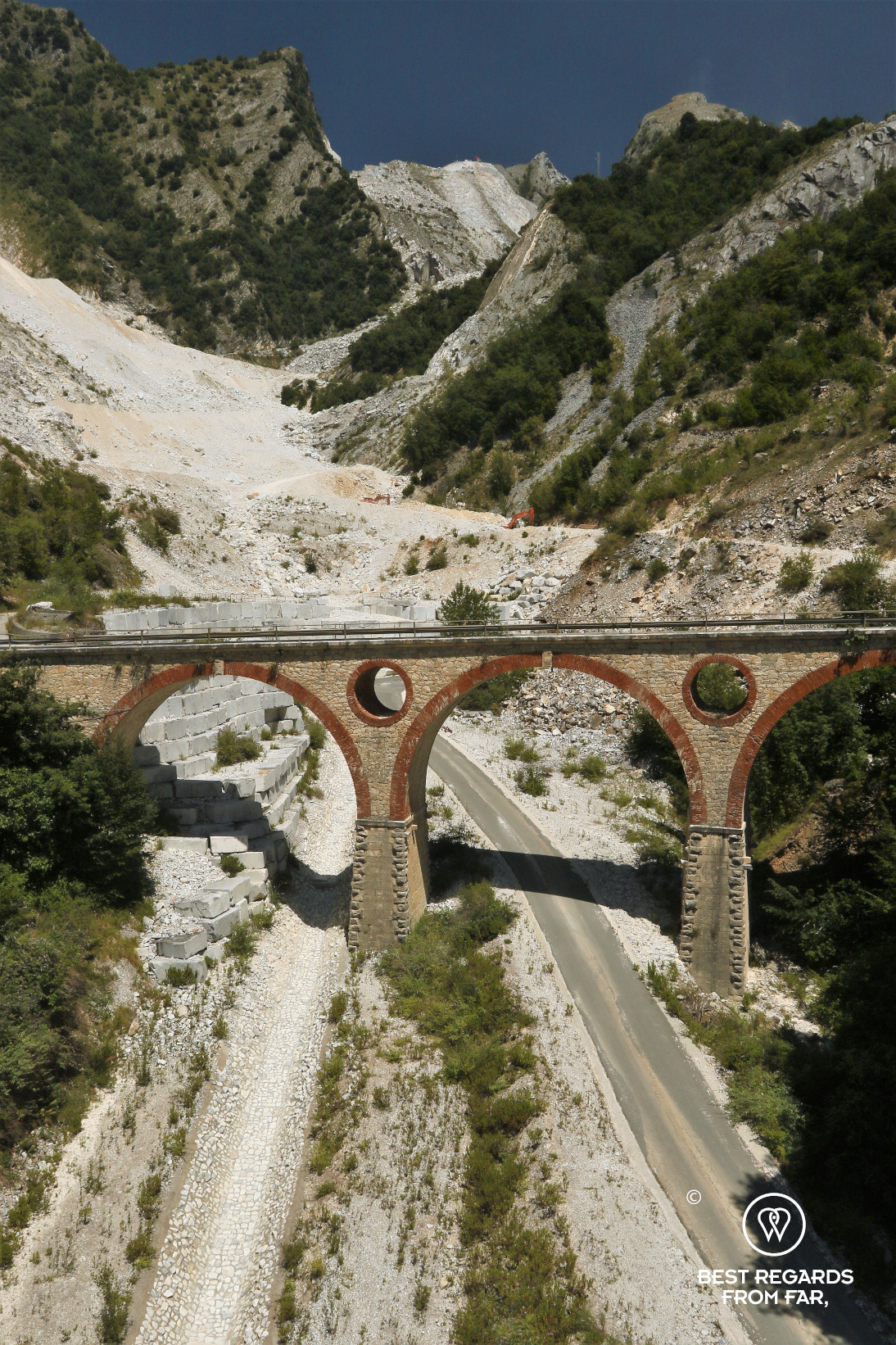 Old bridge over a white road in the mountains of Carrara, Italy