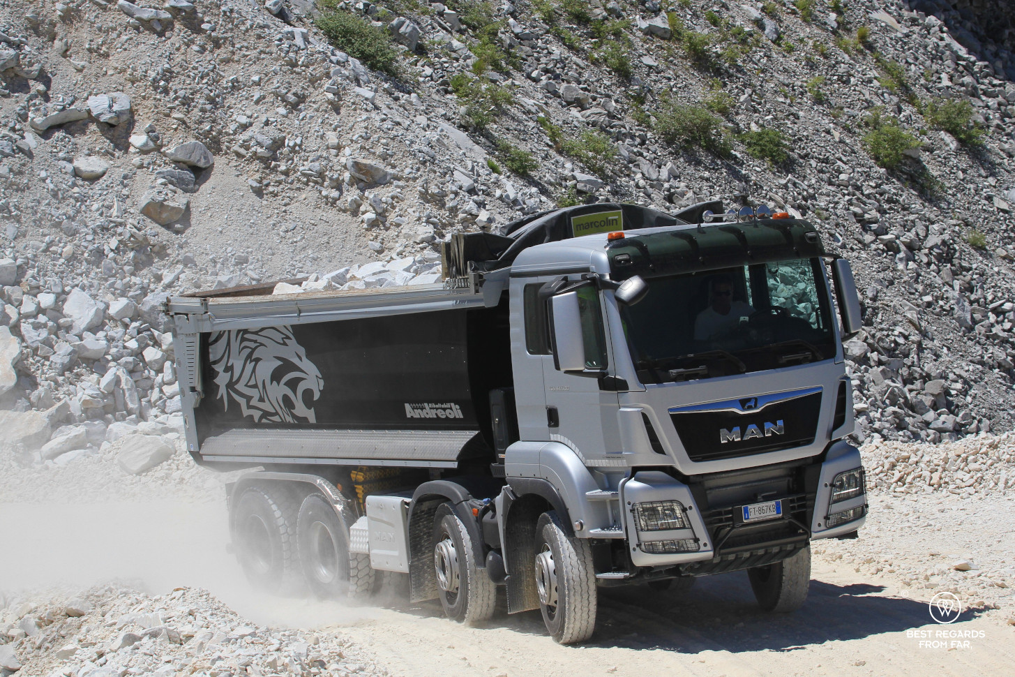Grey truck transporting large blocks of white Carrara marble in the mountains