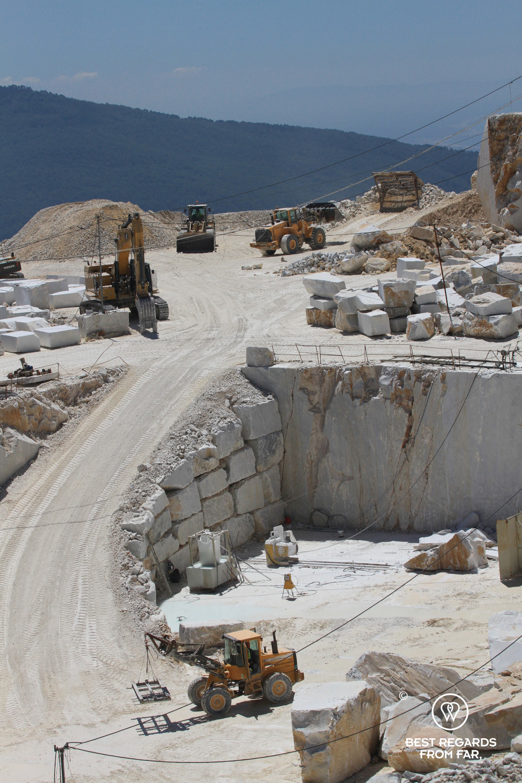 White marbme quarry with tractors driving up and down, Italy