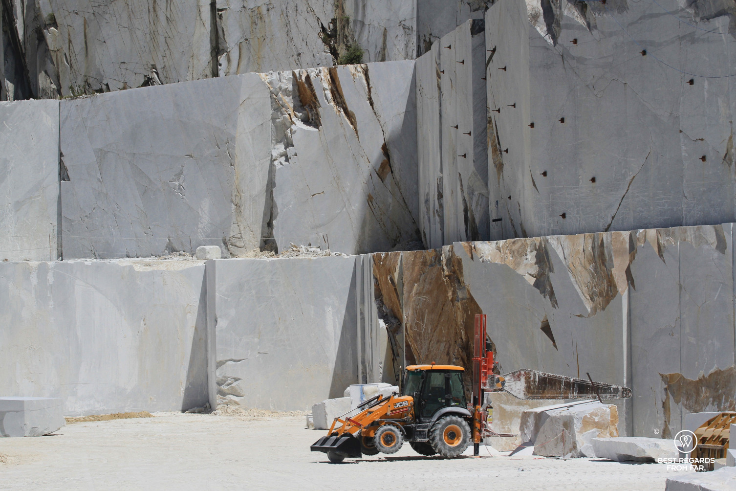 Huge white marble blocks wih an orange tractor in Carrara, Italy