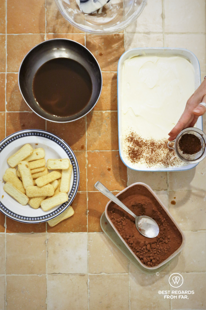 Recipe of tiramisu: chef adding cocoa powder on the layers of cream with other ingredients around: coffee, lady fingers.