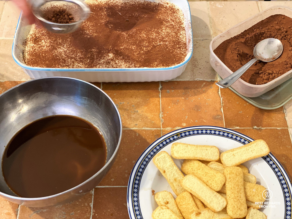 Recipe of tiramisu: adding cacao powder before presenting the tiramisu, with ingredients around (coffee, lady fingers, cacao).