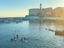 Nervi, the cute suburb of Genoa and its seafront with kayakers playing soccer and the harbour and church tower in the background.