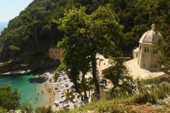 Blue waters, crowded beach and abbey along a foresty mountain slope