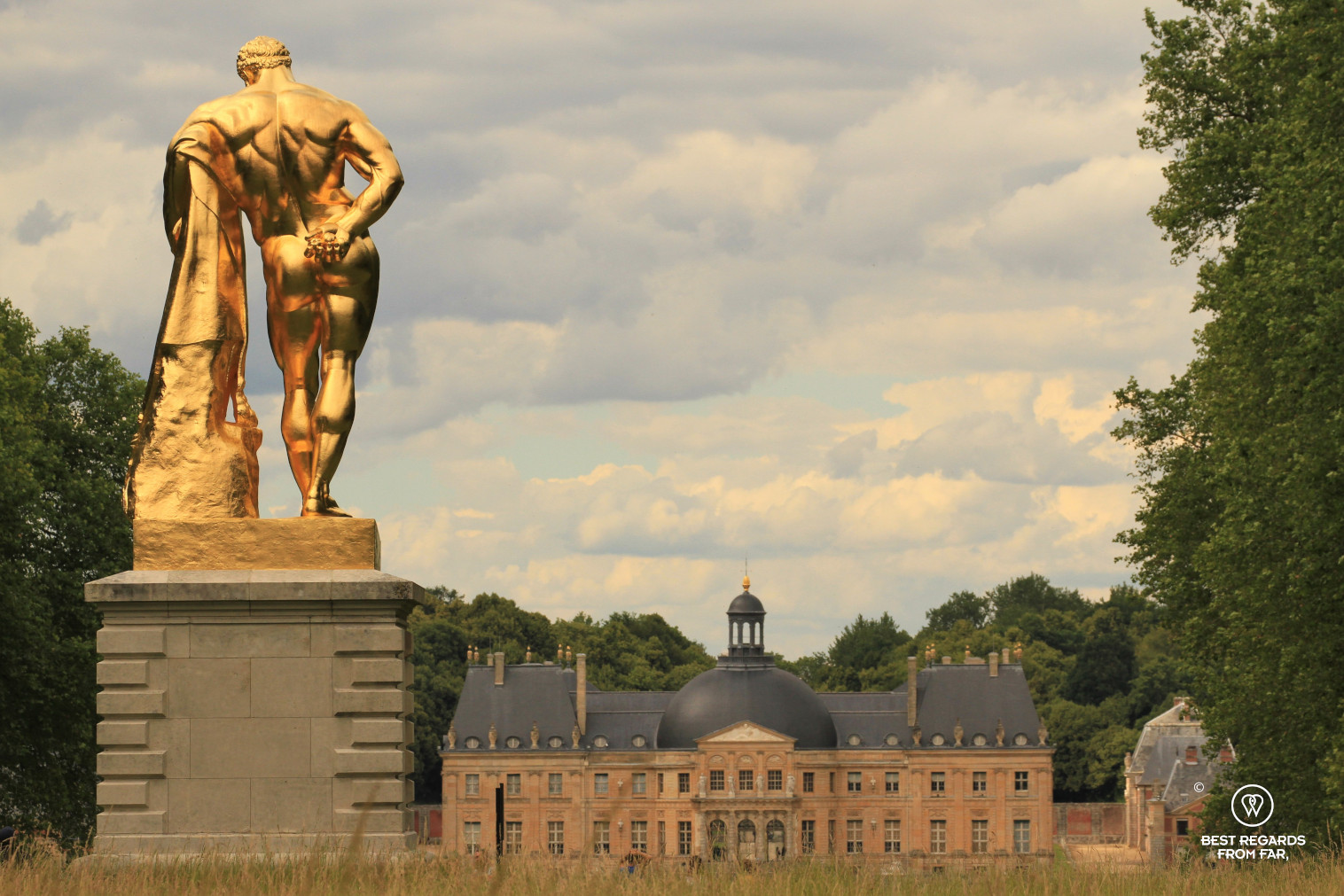 The castle of Vaux le Vicomte seen from the French garden with the golden sculpture of Hercule.