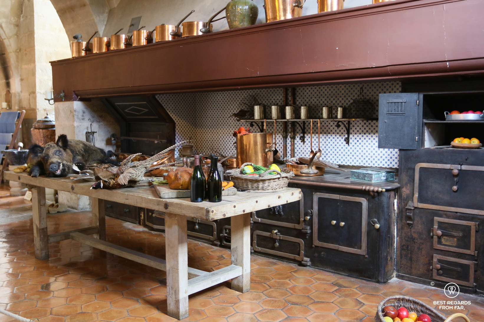 The kitchen of the castle of Vaux le Vicomte, France with its copper pots, abundant food and ancient stove.