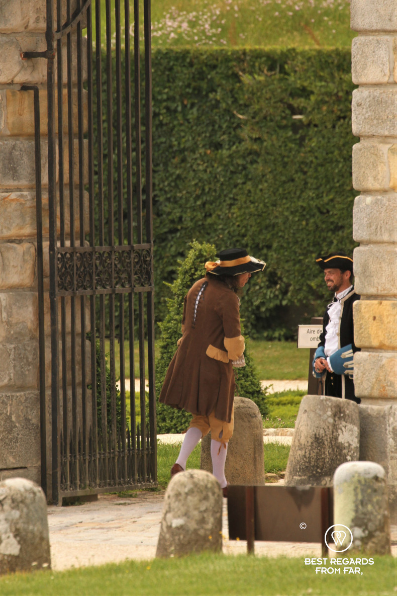 Two men smiling at each other in époque costumes in the gardens of the castle of Vaux le Vicomte, France.