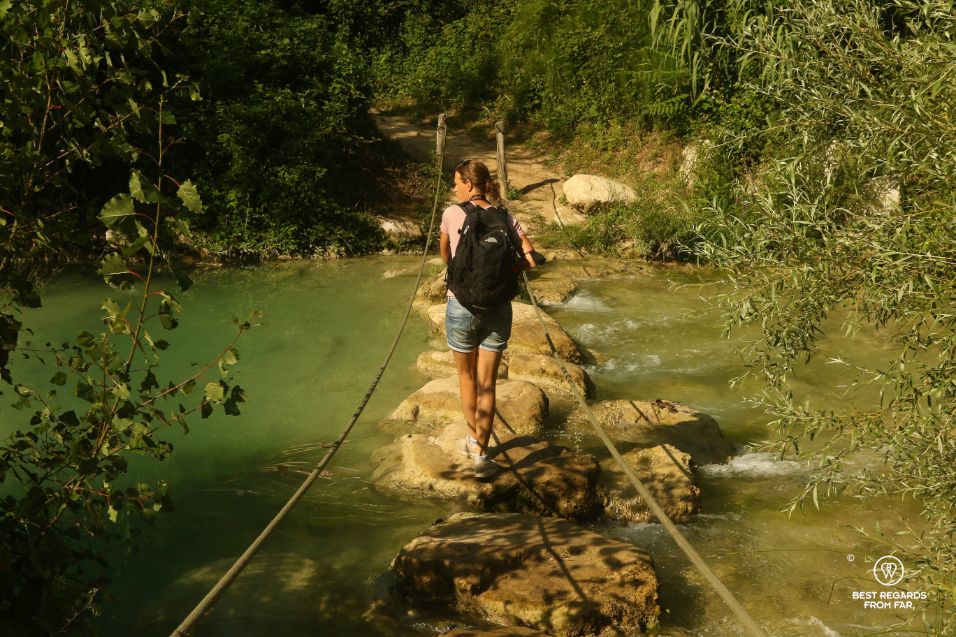 Hiker crossing a foot bridge on the Elsa River, Tuscany, Italy