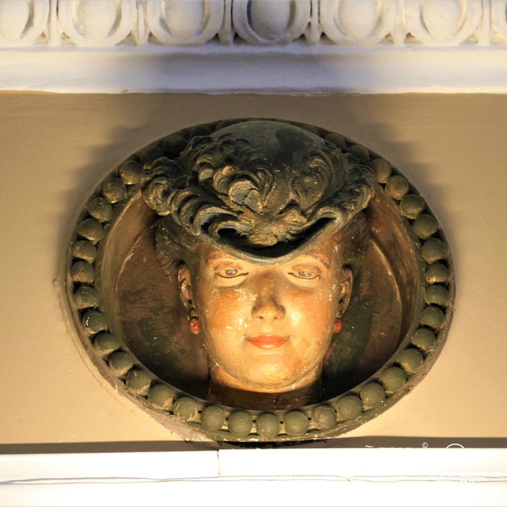 Detail of the lobby of the Bernini Palace, Florence, showing a wooden sculpture of a woman with a hat