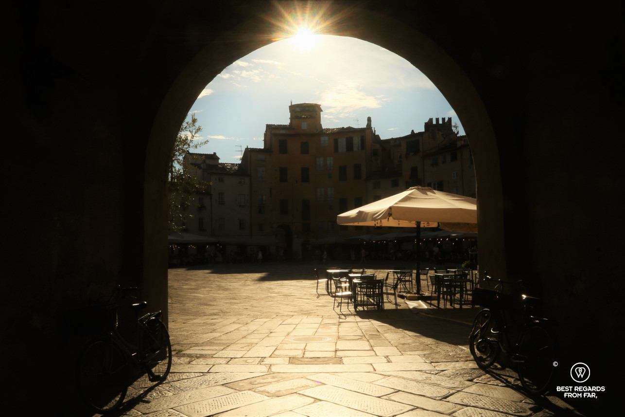 View on the amphitheater, an empty terrace and a parasol in Lucca, Italy