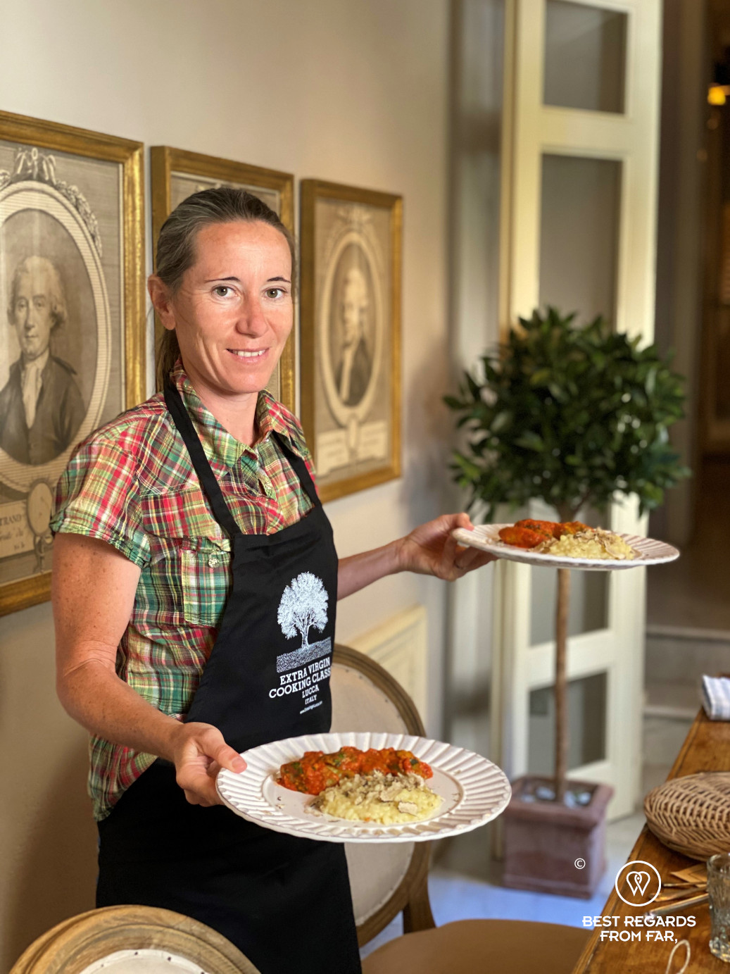 Woman with black apron serving two plates of food in Lucca