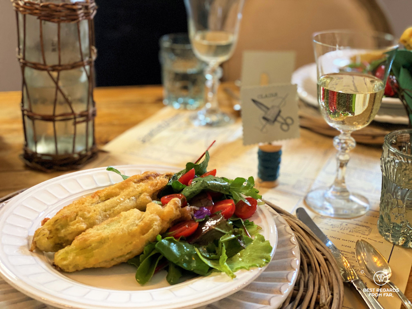 Fried zucchini flowers and salad served on a white plate with white wine
