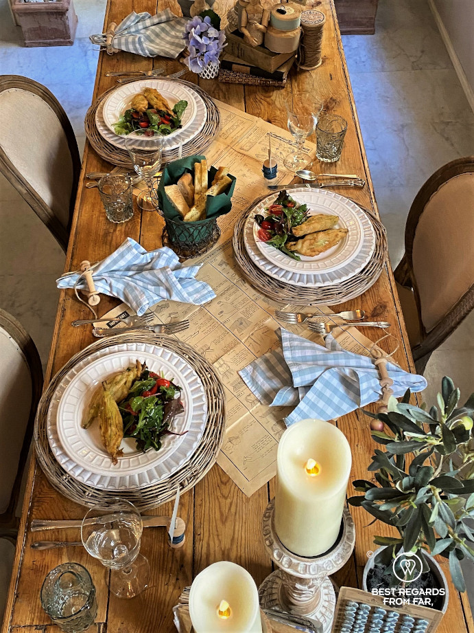 Wooden table with food for three people, candles and napkins