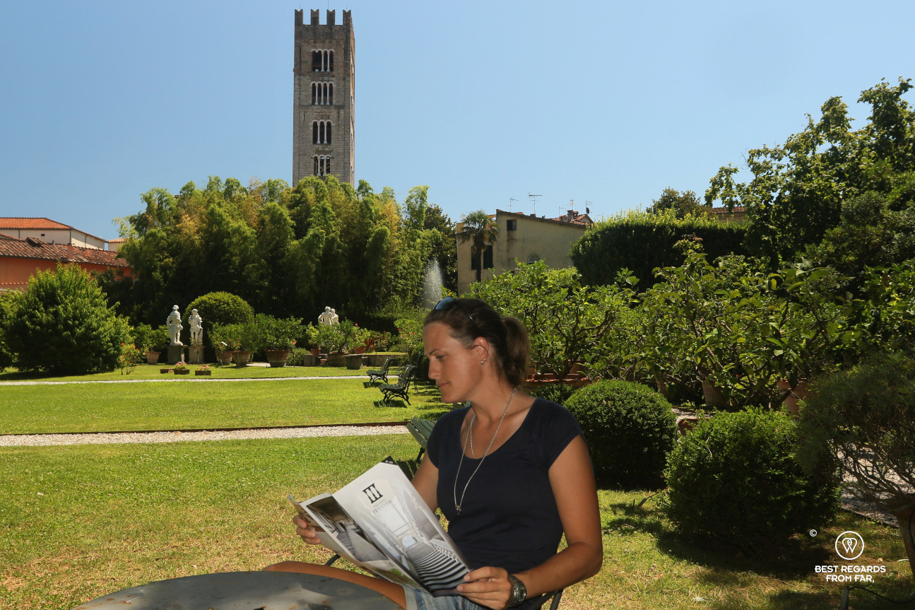 Woman reading a brochure in the green garden of the Pfanner palace, Lucca