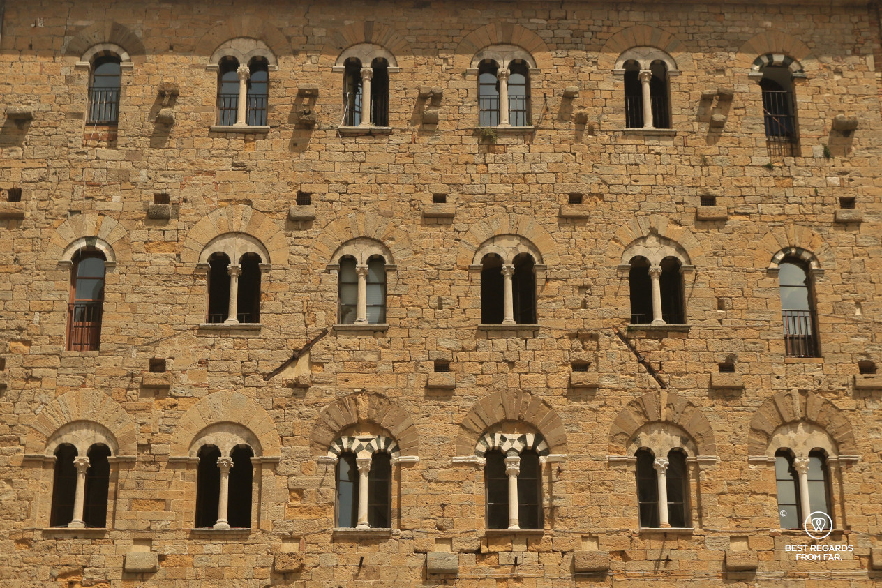 Palace wall with many arched windows in Volterra, Tuscany, Italy