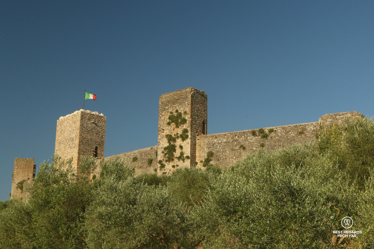 The fortified medieval wall of Monteriggioni with the Italian flag