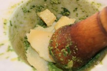 Crushing the Italian cheese with the ingredients in a Carrara marble mortar to make pesto