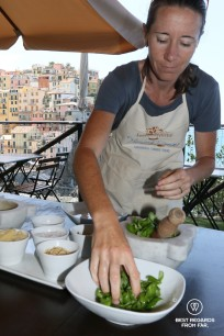 Pesto workshop at Nessun Dorma, Cinque Terre, Italy: drying the basil leaves with Manarola in the background