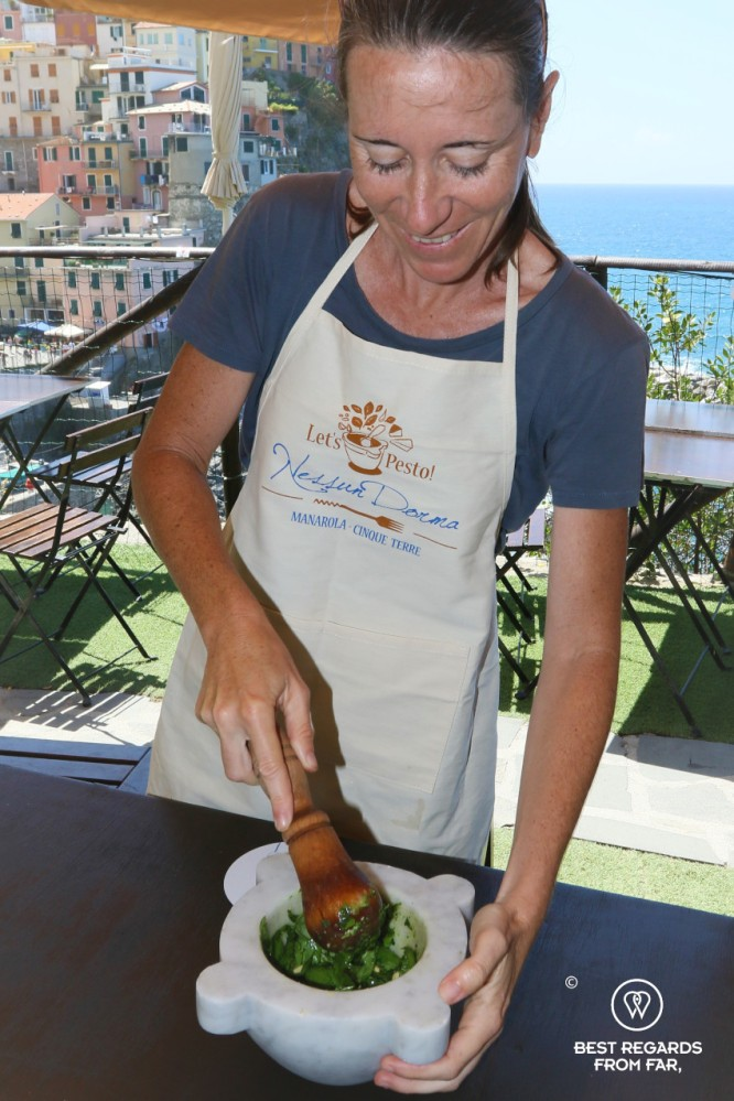 Crushing the pesto in a Carrara marble mortar with a view on Manarola in Cinque Terre, Italy