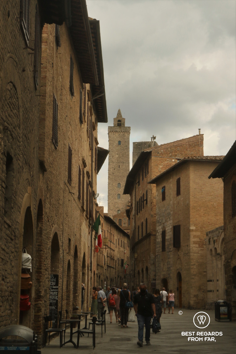 A street of San Gimignano dominated by a medieval tower, Tuscany, Italy