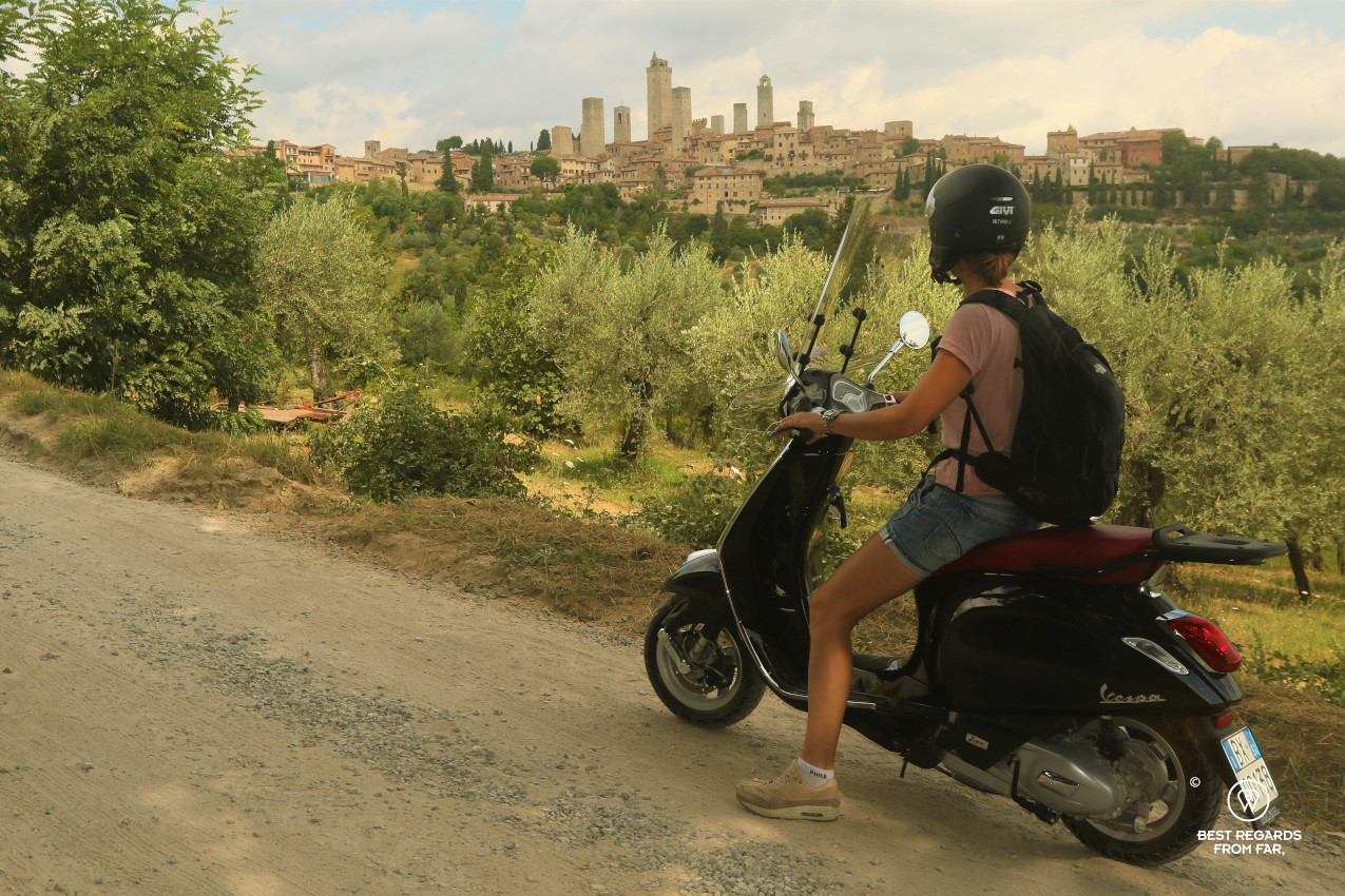Riding a Vespa scooter with the towers of San Gimignano in the background, Tuscany, Italy