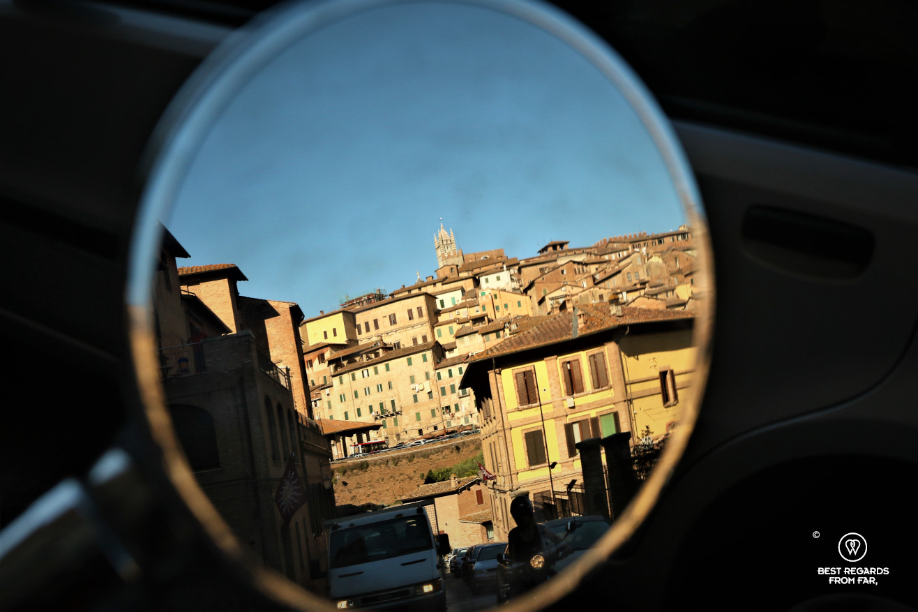 Reflection of Siena in the mirror of a scooter, Italy
