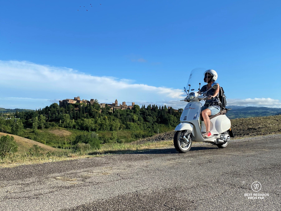 Woman riding a white Vespa scooter by Certaldo, Tuscany, Italy
