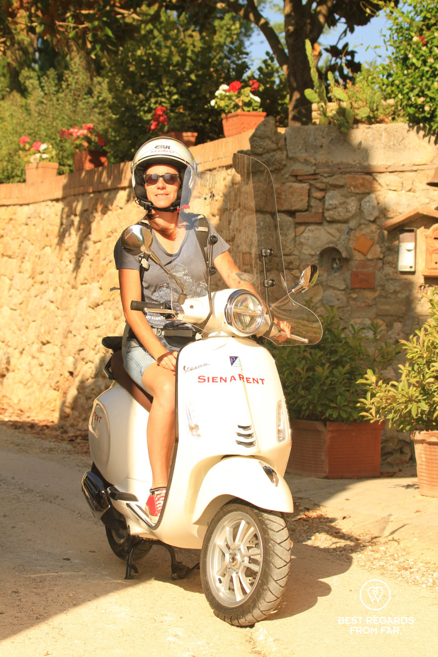A woman in Tuscany on a white Vespa scooter, Italy