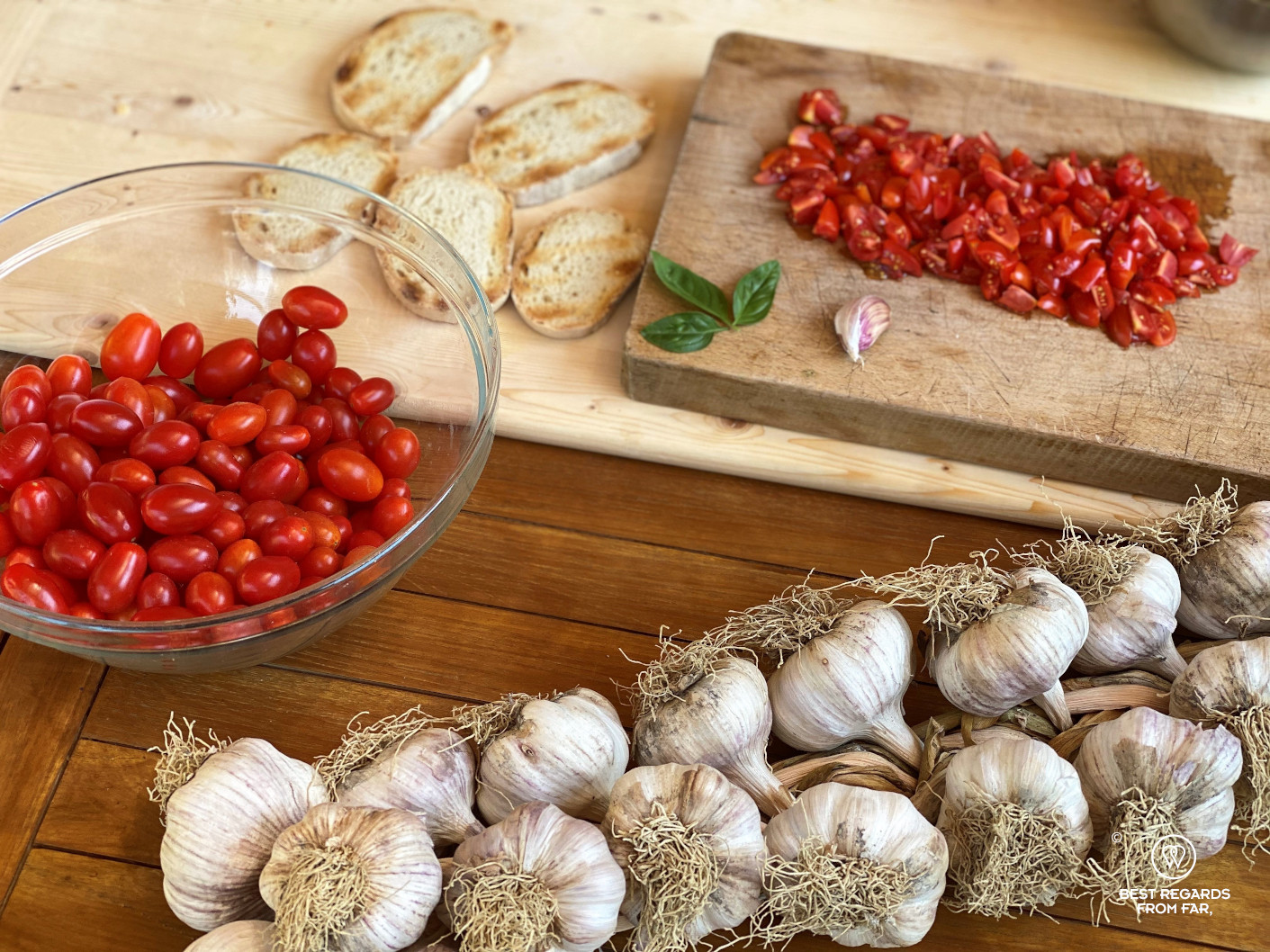 Cherry tomatos, garlic and toasted bread on a wooden board
