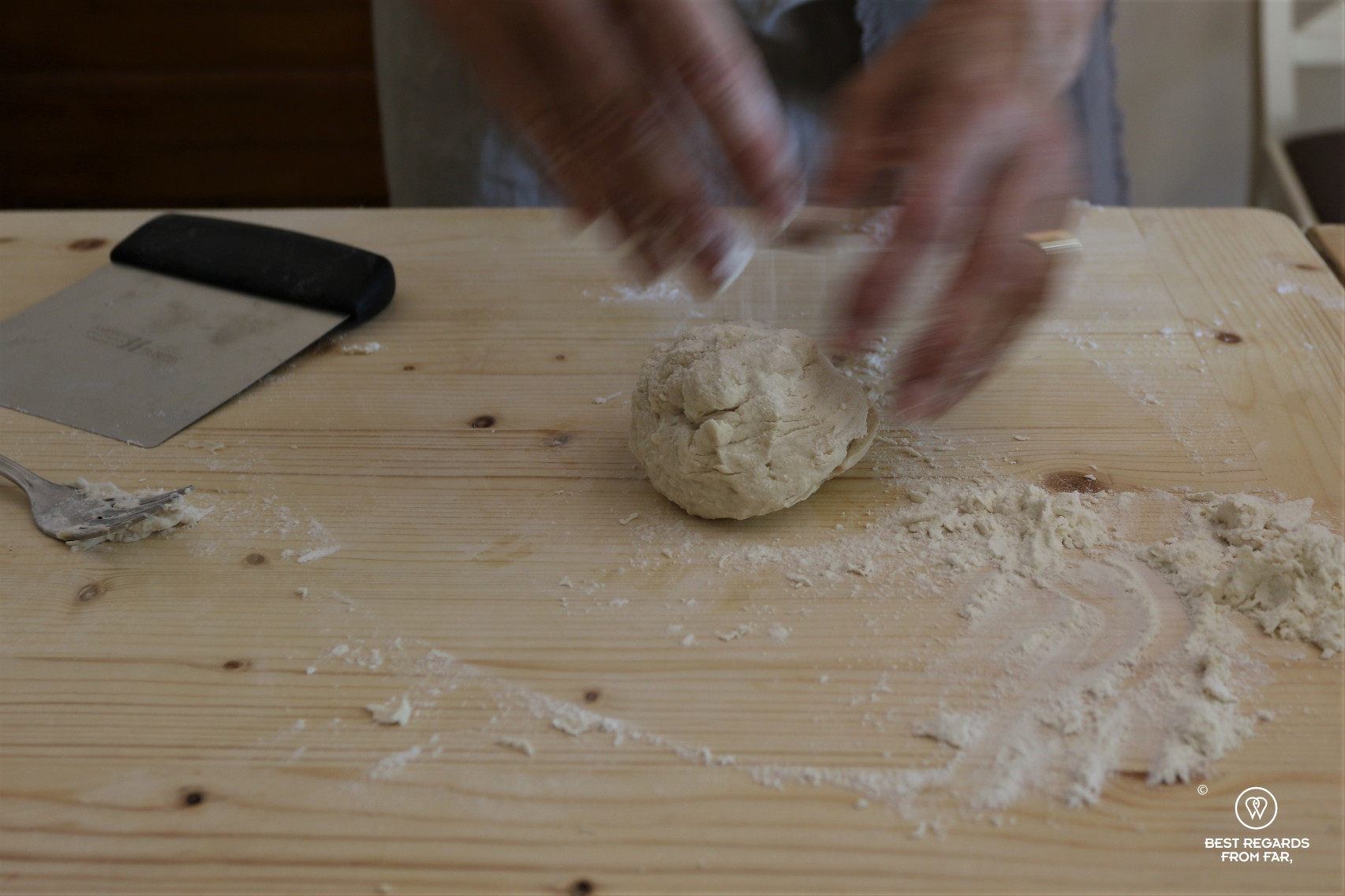 Kneading the dough on a wooden board to make pastas