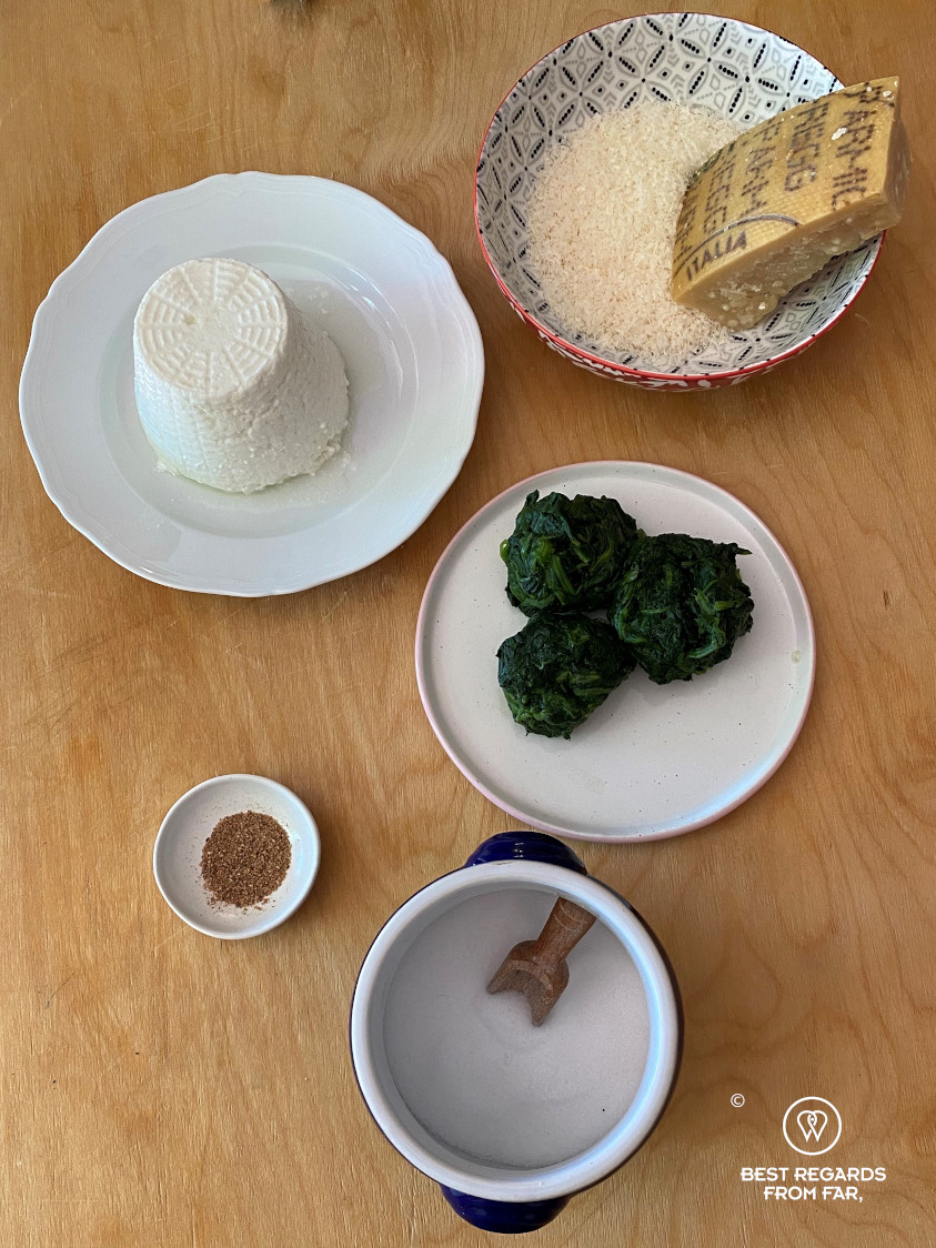 Plates on a wooden table with ricotta, parmagiano, spinach, salt and muscat