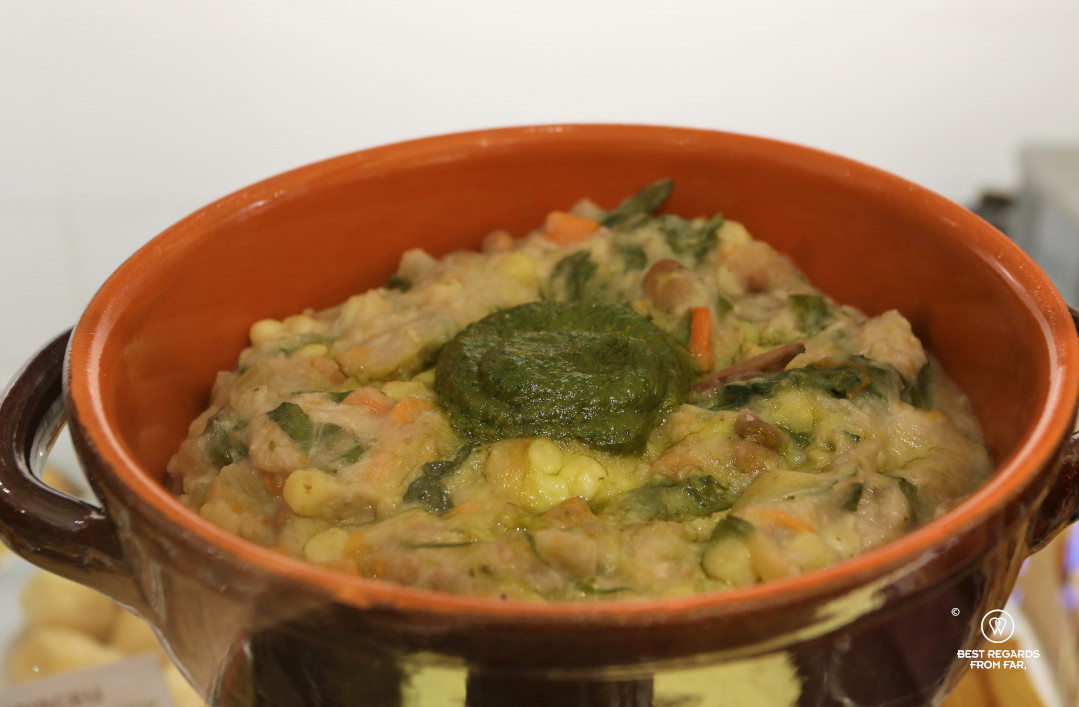 A bowl filled with a thick minestrone soup and pesto on top