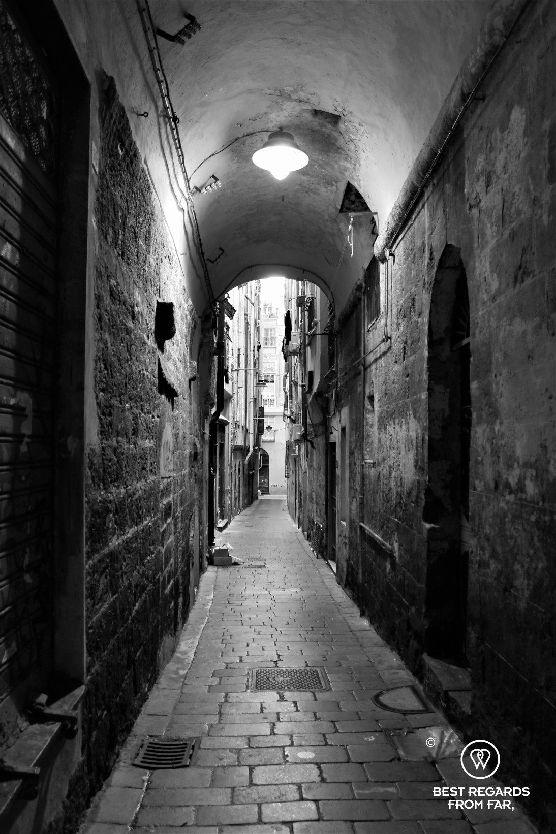 A photo in black and white of a narrow alley in Genoa, Liguria, Italy