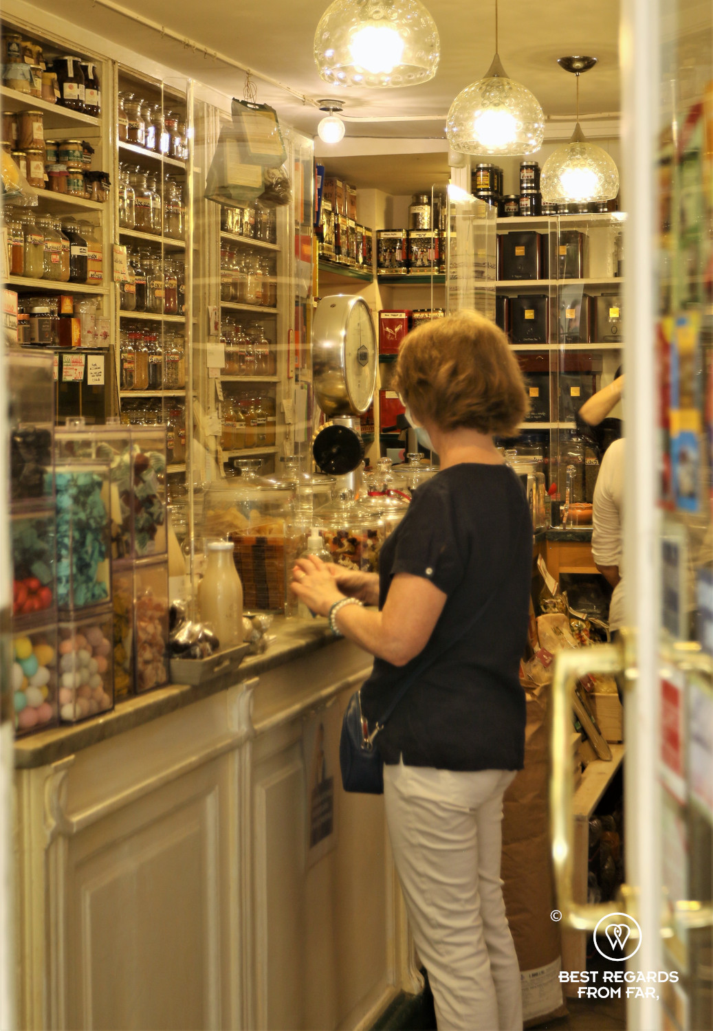 Woman buying spices in an old spice store in Genoa, Italy
