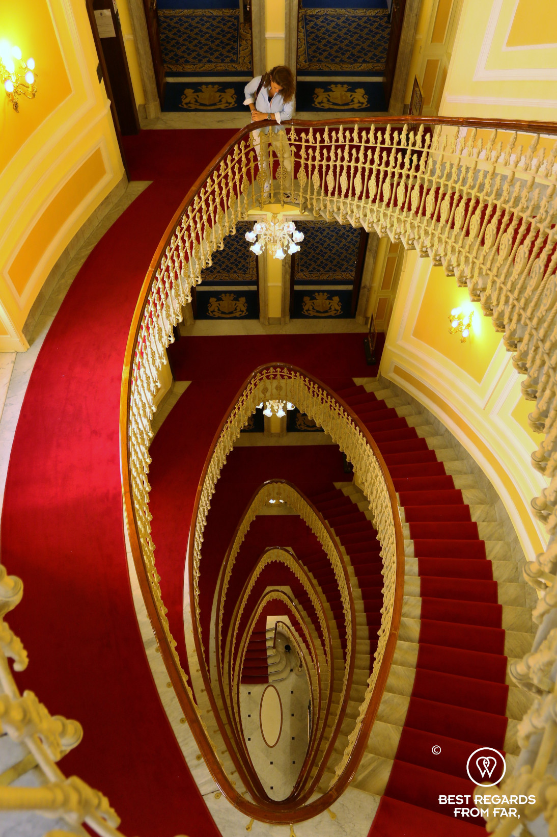 The red-carpetted spiral staircase of the the Hotel Bristol Palace in Genoa, Liguria, Italy