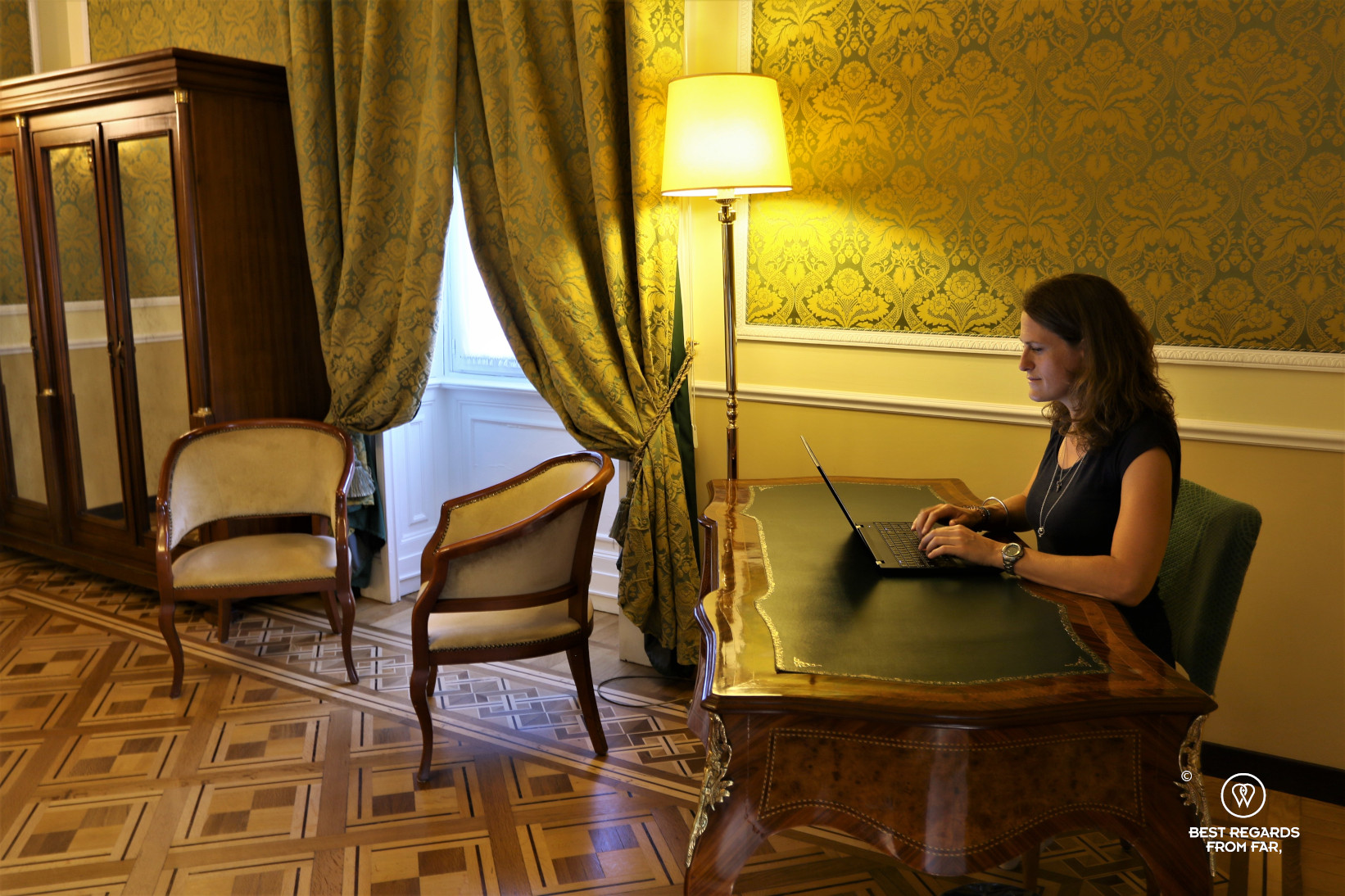 Woman working at a destk in a stylish hotel bedroom in Italy