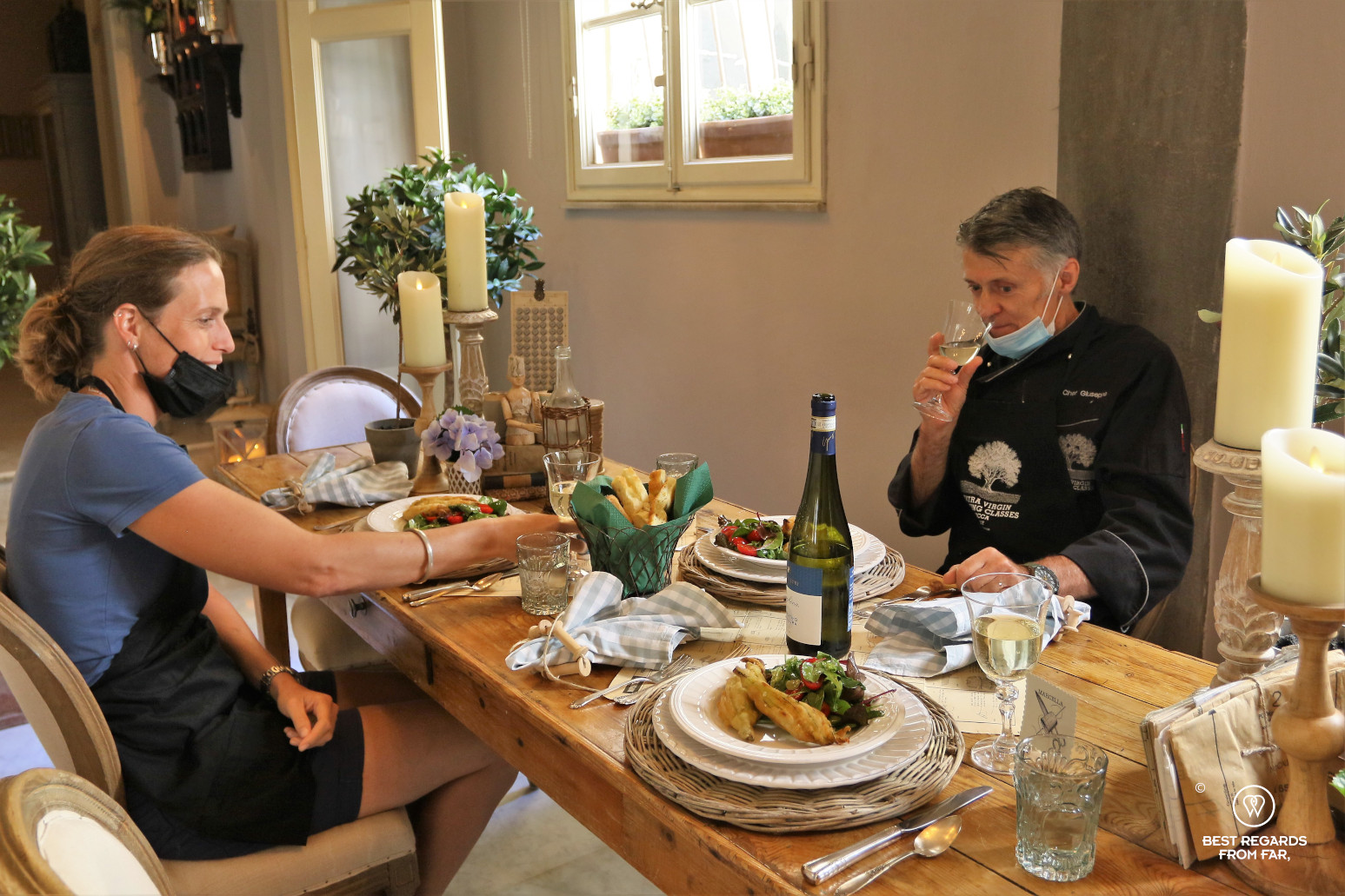 Two people at a nicely decorated table having home-cooked Italian food