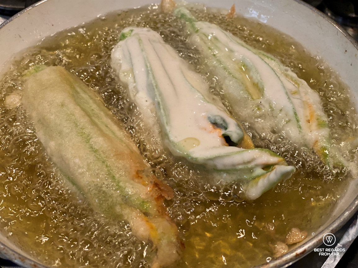 Three zucchini flowers being fried in a pan.