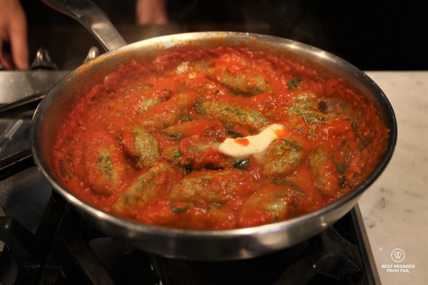 Green spinach and ricotta gnudis in tomato sauce in a large pan on a stove, Italy