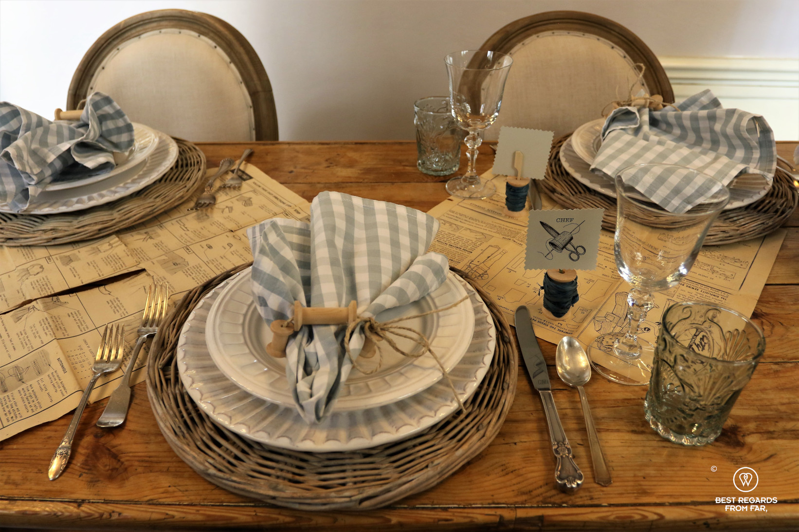 Wooden table set for three people, plates, napkins and glasses.