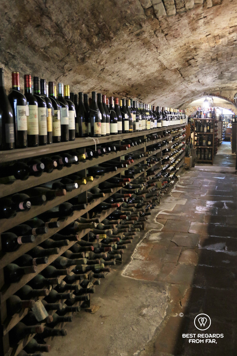 Long rown of bottles of wine stored in a vaulted cellar from Roman times in Italy.