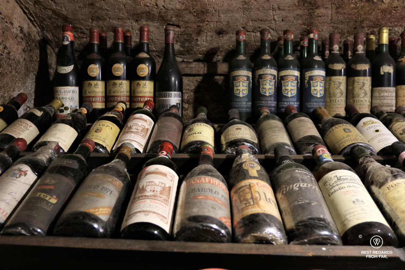 Old bottles of aged red wine in a brick cellar in Lucca, Italy